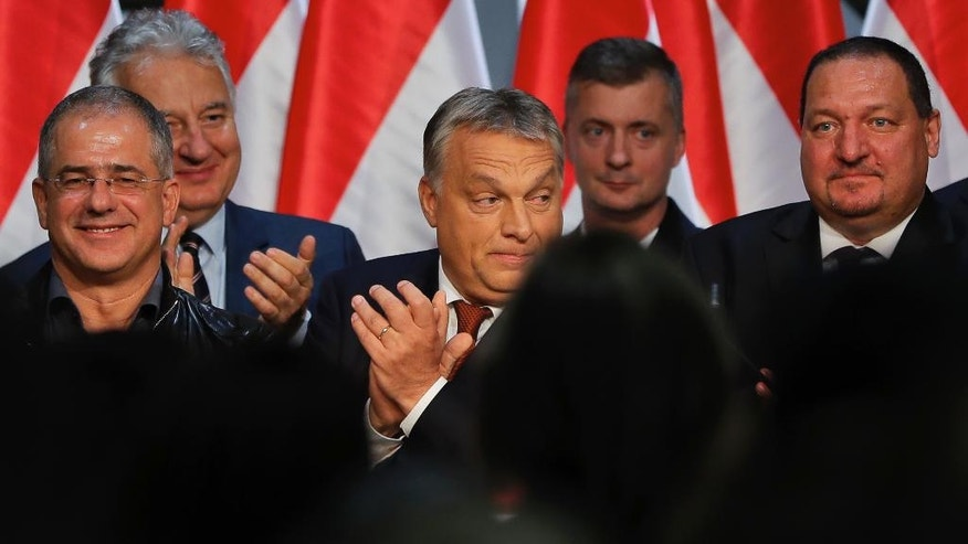 Hungarian Premier Viktor Orban, centre, applauds after delivering a speech in front of supporters in Budapest, Hungary, Sunday, Oct. 2, 2016. Hungarians overwhelmingly supported the government in a referendum on Sunday called to oppose any future, mandatory European Union quotas for accepting relocated asylum seekers but nearly complete official results showed the ballot was invalid due to low voter turnout. (AP Photo/Vadim Ghirda)