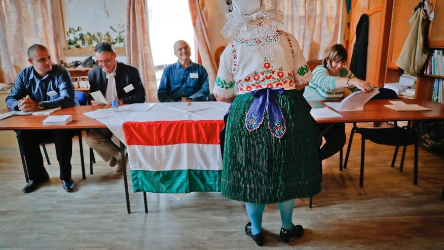 Edit Piros, an ethnic Hungarian from Romania, who moved to Hungary from Transylvania, central Romania, receives the ballot paper before voting in the referendum in the village of Veresegyhaz, Hungary, Sunday, Oct. 2, 2016. Hungarians vote in a referendum which Prime Minister Viktor Orban hopes will give his government the popular support it seeks to oppose any future plans by the European Union to resettle asylum seekers among its member states. (AP Photo/Vadim Ghirda)
