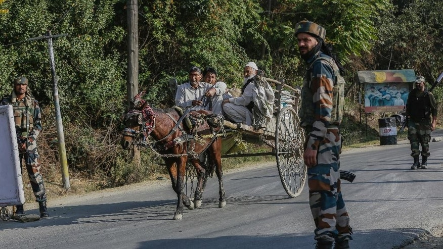 An Indian army soldier guards as Kashmiri villagers pass on horse cart outside the base camp which was attacked by suspected militants at Baramulla, northwest of Srinagar, Indian controlled Kashmir, Monday, Oct. 3, 2016. A gun battle with a group of militants who attacked an Indian army camp in the Indian portion of Kashmir has ended early Monday morning, police said. (AP Photo/Mukhtar Khan)