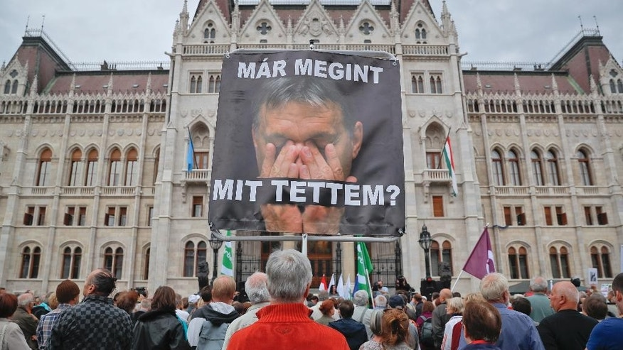 "A man holds a poster of Hungarian Premier Viktor Orban that reads ""What have I done again"" during a protest by opposition parties against Orban's policies on migrants in Budapest, Hungary, Sunday, Oct. 2, 2016. Hungarians vote in a referendum which Prime Minister Viktor Orban hopes will give his government the popular support it seeks to oppose any future plans by the European Union to resettle asylum seekers among its member states. (AP Photo/Vadim Ghirda)"