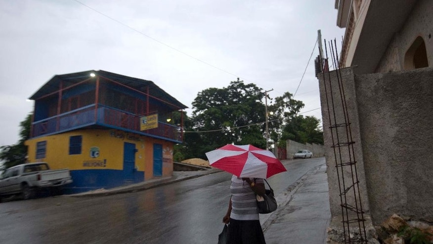 A woman walks with an umbrella as protection from a light rain, in Port-au-Prince, Haiti, Monday, Oct. 3, 2016. Major Hurricane Matthew is slowly churning northward across the Caribbean and meteorologists say the powerful storm is expected to approach Jamaica and southwest Haiti by Monday night. (AP Photo/Dieu Nalio Chery)