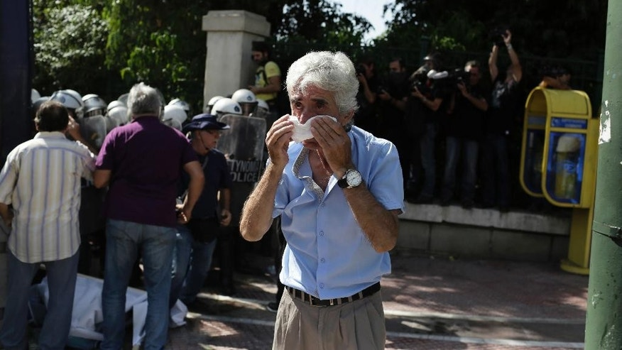 A pensioner protects his face after Greek police fired pepper spray at retirees taking part in an anti-austerity protest against pension cuts in central Athens near the prime minister's office on Monday, Oct. 3, 2016. About 1,000 people, took part in Monday's protest.(AP Photo/Petros Giannakouris)