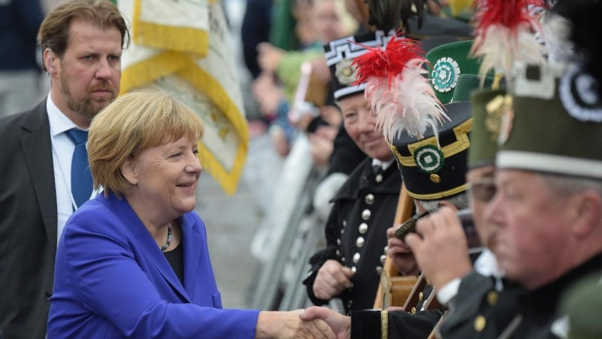 German Chancellor Angela Merkel shakes hands with miners during the celebrations of the 26th anniversary of the German unity in Dresden, Germany, Monday, Oct. 3, 2016. (AP Photo/Jens Meyer)