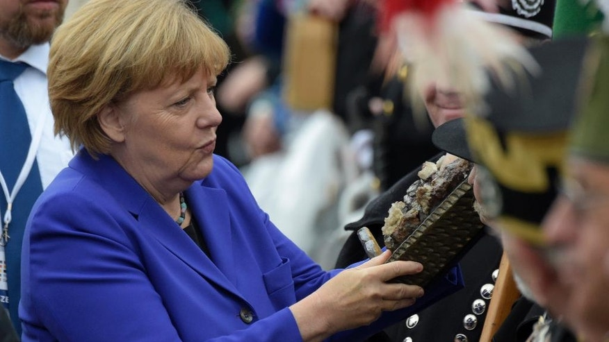 German Chancellor Angela Merkel looks at a miner's outfit during the celebrations of the 26th anniversary of the German unity in Dresden, Germany, Monday, Oct. 3, 2016. (AP Photo/Jens Meyer)