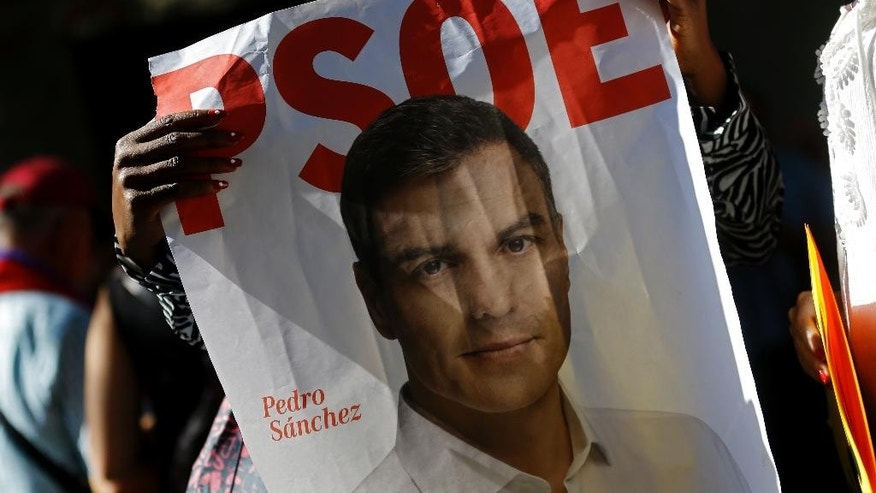 A woman holds a poster with the photograph of Spain's Socialist party leader Pedro Sanchez as she gathers with other people outside the party headquarters in Madrid, Saturday, Oct. 1, 2016. Spain's Socialist party is facing strong internal discord as they vote to decide if they will keep or oust their leader Pedro Sanchez, who has been leading opposition to acting conservative Prime Minister Mariano Rajoy's efforts to build a minority government and end a nine-month political deadlock. (AP Photo/Francisco Seco)