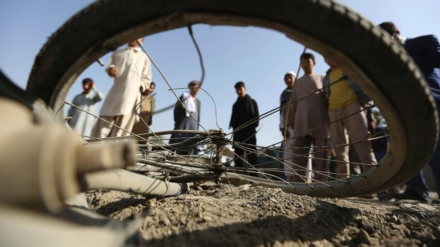 Afghan civilians watch a damaged bicycle after a bomb explosion targeted an army vehicle in Kabul, Afghanistan, Monday, Oct. 3, 2016, A police said an Afghan soldier was killed in the bicycle bomb blast. (AP Photo/Rahmat Gul)