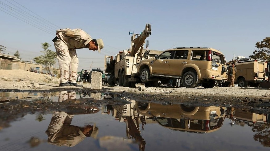 An Afghan security personnel inspects the site of a bicycle bomb explosion targeted an army vehicle in Kabul, Afghanistan, Monday, Oct. 3, 2016.  A police officer said an Afghan soldier was killed in the blast. (AP Photo/Rahmat Gul)