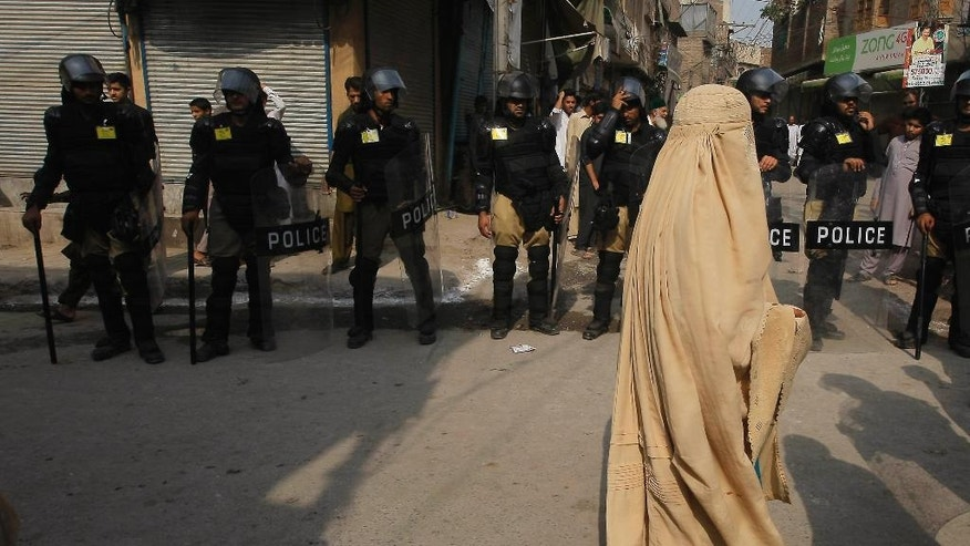 Pakistani police officers stand guard outside a mosque during Shiite Muslims' congregation during the mourning month Muharrum in Peshawar, Pakistan, Tuesday, Oct. 4, 2016. Authorities are taking extra precautionary measures to avert any terrorist attempt during Muharram, the first month of the Islamic calendar, which is observed around the world for ten days of mourning in remembrance of the martyrdom of Imam Hussein, the grandson of Prophet Mohammed. (AP Photo/K.M. Chaudary)