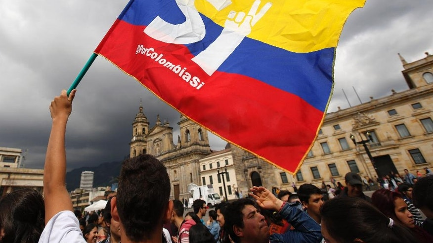 A supporter of the peace deal signed between the Colombian government and rebels of the Revolutionary Armed Forces of Colombia, FARC, wave a flag during a rally in front of Congress, in Bogota, Colombia, Monday, Oct. 3, 2016.  Colombians  rejected a peace deal with leftist rebels of the Revolutionary Armed Forces of Colombia, FARC, by a razor-thin margin in a national referendum Sunday, dismissing years of negotiations and delivering a setback to President Juan Manuel Santos. (AP Photo/Fernando Vergara)