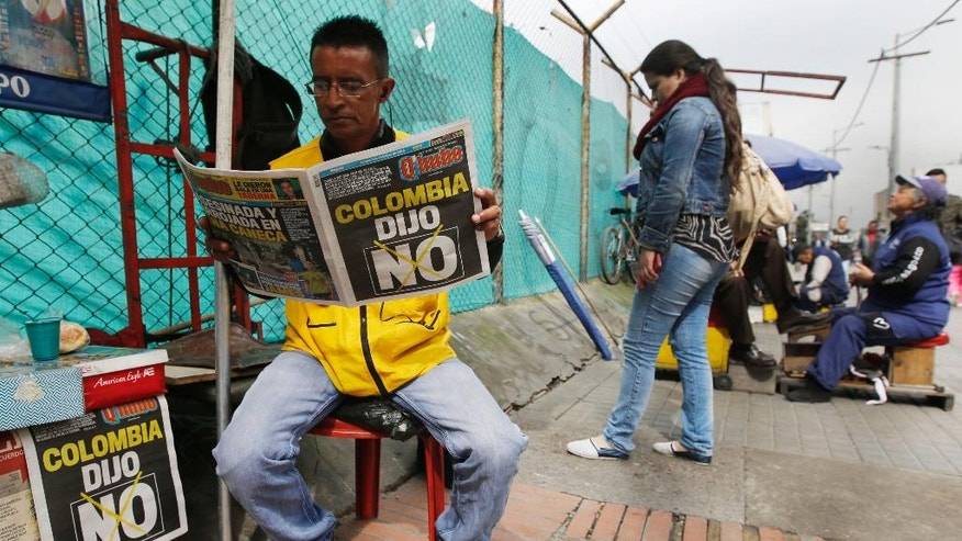 "A man reads a newspaper with the headline that reads in Spanish: ""Colombia said No"" in Bogota, Colombia, Monday, Oct. 3, 2016. Voters rejected a peace deal with leftist rebels of the Revolutionary Armed Forces of Colombia, FARC, by a razor-thin margin in a national referendum Sunday, dismissing years of  negotiations and delivering a setback to President Juan Manuel Santos. Final results showed that 50.2 percent opposed the accord, while 49.8 percent favored it. (AP Photo/Fernando Vergara)"