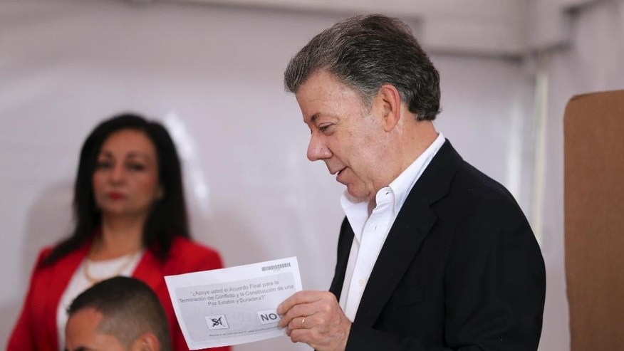 Colombia's President Juan Manuel Santos prepares to cast his ballot in a referendum to decide whether or not to support the peace deal he signed with rebels of the Revolutionary Armed Forces of Colombia, FARC, in Bogota, Colombia, Sunday, Oct. 2, 2016.   (AP Photo/Fernando Vergara)
