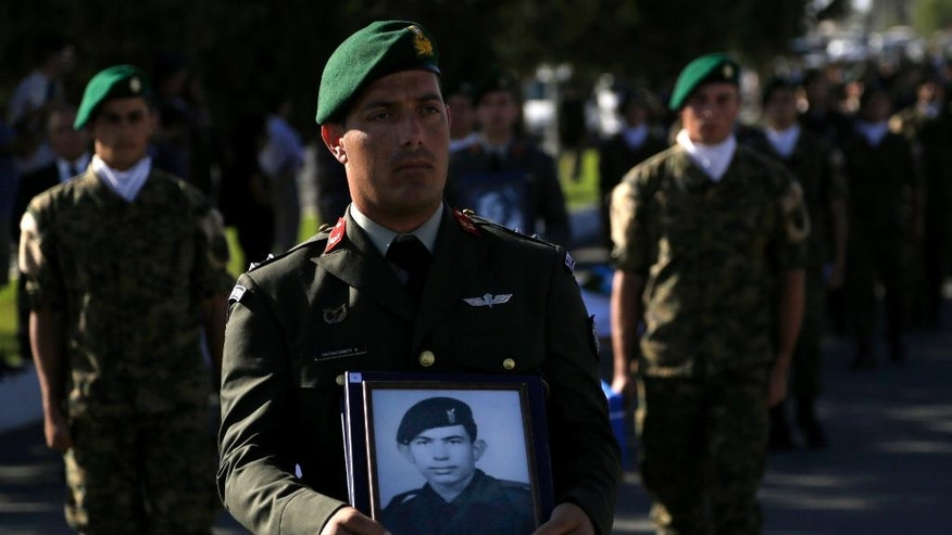 Greek soldiers carry the coffins and the photographs of the Greek commandos who were killed in a transport aircraft during the Turkish invasion on 1974, during a handover remains ceremony at the wartime memorial on Nicosia's outskirts in divided island of Cyprus, Tuesday, Oct. 4, 2016. The remains of 16 Greek commandos founded inside the Noratlas' aircraft during an excavation and after identified through DNA analysis and returned to their families. Greek military transport aircraft that was brought down by friendly fire in the opening days of Turkey's invasion of the island 42 years ago. (AP Photo/Petros Karadjias)