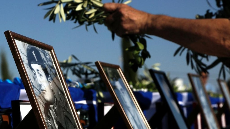 A relative of a Greek soldier leaves olive branches on the coffins with photographs of the Greek commandos who were killed in a transport aircraft during the Turkish invasion on 1974, during a handover remains ceremony at the wartime memorial on Nicosia's outskirts in divided island of Cyprus, Tuesday, Oct. 4, 2016. The remains of 16 Greek commandos founded inside the Noratlas' aircraft during an excavation and after identified through DNA analysis and returned to their families. Greek military transport aircraft that was brought down by friendly fire in the opening days of Turkey's invasion of the island 42 years ago. (AP Photo/Petros Karadjias)