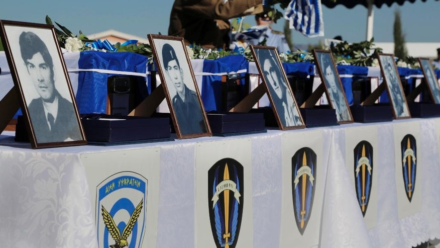 An elderly man leaves Greek and Cypriot flags on the coffins of the Greek commandos who were killed in a transport aircraft during the Turkish invasion on 1974, during a handover remains ceremony at the wartime memorial on Nicosia's outskirts in divided island of Cyprus, Tuesday, Oct. 4, 2016. The remains of 16 Greek commandos founded inside the Noratlas' aircraft during an excavation and after identified through DNA analysis and returned to their families. Greek military transport aircraft that was brought down by friendly fire in the opening days of Turkey's invasion of the island 42 years ago. (AP Photo/Petros Karadjias)