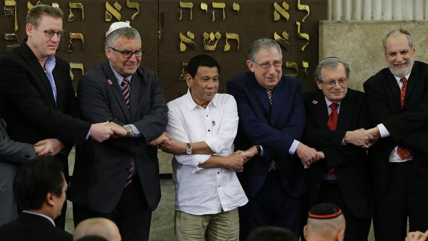 Philippine President Rodrigo Duterte, 3rd from left, link arms with Israeli Ambassador Effie Ben Matityau, 2nd from left, and members of the Jewish Association of the Philippines, during a meeting at the Beit Yaacov Synagogue, The Jewish Association of the Philippines in Makati, south of Manila, Philippines on Tuesday, Oct. 4, 2016. Duterte has apologized to Jews worldwide after his remarks drawing comparisons between his bloody anti-drug war and Hitler and the Holocaust sparked shock and outrage. (AP Photo/Aaron Favila, Pool)