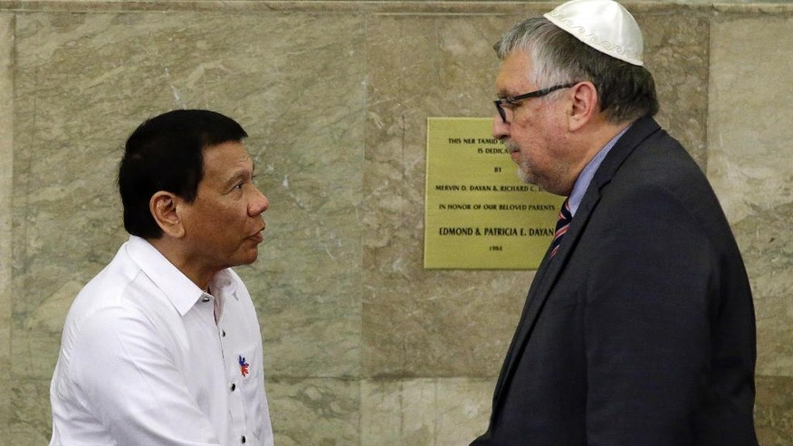 Philippine President Rodrigo Duterte, left, shake hands with Israeli Ambassador Effie Ben Matityau, during his visit to the Beit Yaacov Synagogue, Jewish Association of the Philippines in Makati, south of Manila, Philippines on Tuesday, Oct. 4, 2016. Duterte has apologized to Jews worldwide after his remarks drawing comparisons between his bloody anti-drug war and Hitler and the Holocaust sparked shock and outrage. (AP Photo/Aaron Favila, Pool)