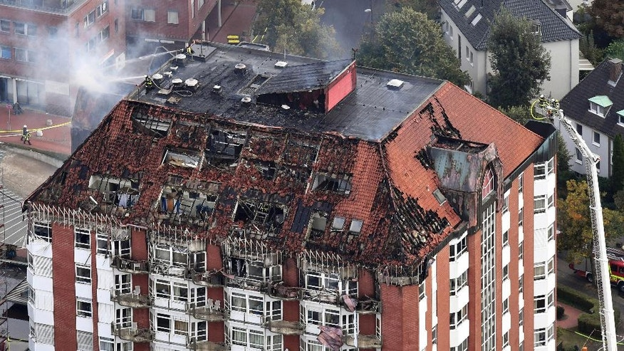 FILE - In this Sept. 30, 2016 file photo, an aerial view shows firefighters working on the burned-out attic of the Bergmannsheil hospital in Bochum, Germany. Prosecutors said on Tuesday, Oct. 4, 2016 that a fire at the hospital, in which two people died, was caused by a patient pouring disinfectant over herself and setting it alight in an attempt to kill herself. (Federico Gambarini/dpa via AP, File)