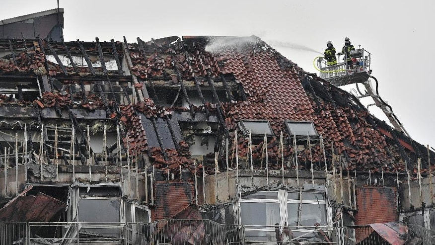 FILE - In this Sept. 30, 2016 file photo, firefighters are busy extinguishing a blaze on the roof of the Bergmannsheil hospital in Bochum, western Germany. Prosecutors said on Tuesday, Oct. 4, 2016 that the fire at the hospital, in which two people died, was caused by a patient pouring disinfectant over herself and setting it alight in an attempt to kill herself. (AP Photo/Martin Meissner, File)