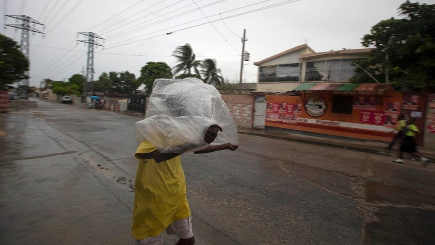 A man crosses a street using a garbage bag as protection from a light rain, in Port-au-Prince, Haiti, Monday, Oct. 3, 2016. Major Hurricane Matthew is slowly churning northward across the Caribbean and meteorologists say the powerful storm is expected to approach Jamaica and southwest Haiti by Monday night. (AP Photo/Dieu Nalio Chery)