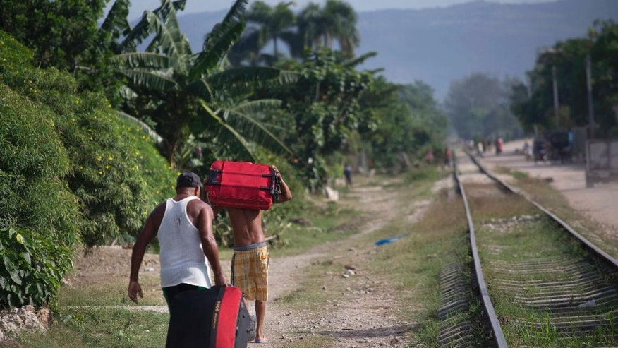 People carry suitcases as they move to a safer area before the arrival of Hurricane Matthew, in the village Paraguay, Guantanamo, Cuba, Monday, Oct. 3, 2016. A hurricane warning is in effect for Jamaica, Haiti, and the Cuban provinces of Guantanamo, Santiago de Cuba, Holguin, Granma and Las Tunas - as well as the southeastern Bahamas. (AP Photo/Ramon Espinosa)
