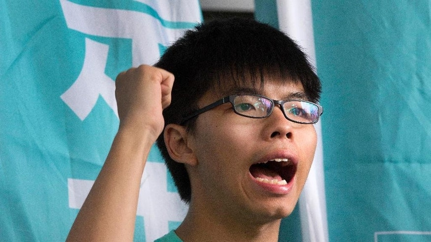 FILE - In this Aug. 15, 2016 file photo, Hong Kong student pro-democracy activist Joshua Wong shouts slogans outside a magistrate's court in Hong Kong. Wong has been detained by Thai officials after arriving to give a talk at a university, his political party said. Demosisto said in a Facebook post that the party was unable to contact Wong after he arrived at Bangkok's main airport late Tuesday, Oct. 4, 2016. The group said it got word early Wednesday, Oct. 5 from a Thai student activist who was expected to meet Wong that he had been detained at Suvarnabhumi Airport after Thai authorities received a request from the Chinese government about his visit. (AP Photo/Vincent Yu, File)