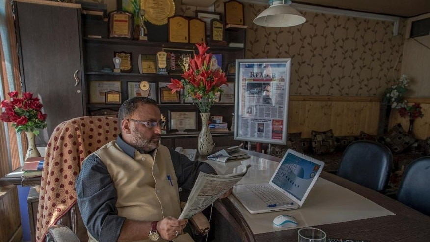 "Hayat Mohammad Bhat,  editor in chief of Kashmir Reader reads newspaper inside his office in Srinagar, Indian controlled Kashmir, Tuesday, Oct. 4, 2016. The English daily ""Kashmir Reader"" did not publish for the second straight day on Tuesday, following a government order over the weekend for its owner to halt publication. (AP Photo/Dar Yasin)"