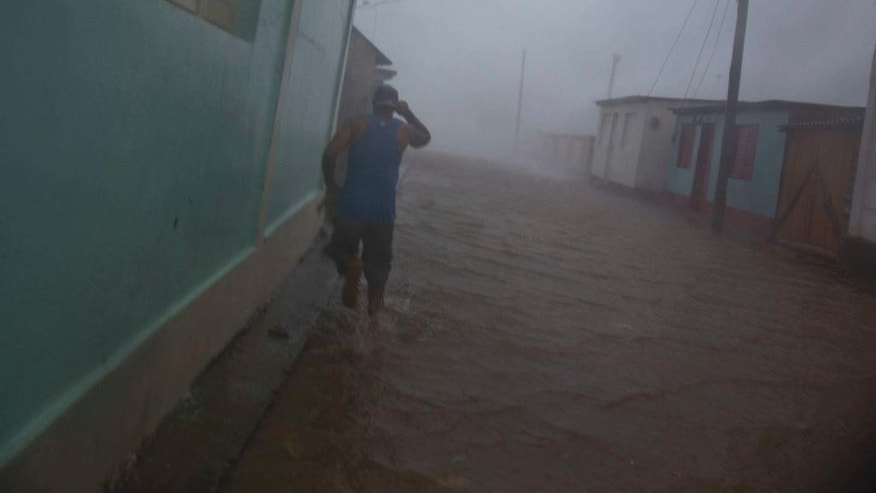 A resident runs in as flooded street as Hurricane Matthew roars over Baracoa, Cuba, Tuesday, Oct. 4, 2016. The dangerous Category 4 storm blew ashore around dawn in Haiti. It unloaded heavy rain as it swirled on toward a lightly populated part of Cuba and the Bahamas. (AP Photo/Ramon Espinosa)