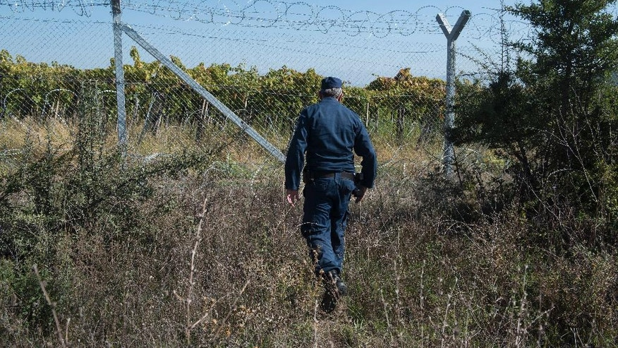 A Greek police officer patrols next to the border fence between Greece and Macedonia, near the northern Greek border station of Idomeni, on Monday, Oct. 3, 2016. Despite Macedonia's construction of a fence, dozens of people try to sneak across the border every day, hoping to make their way to Europe's prosperous heartland. Police have been detaining about 50 people daily, and arresting members of smuggling gangs that promise to get migrants to their destinations. About 60,000 refugees and other migrants are trapped in financially-struggling Greece. (AP Photo/Giannis Papanikos)
