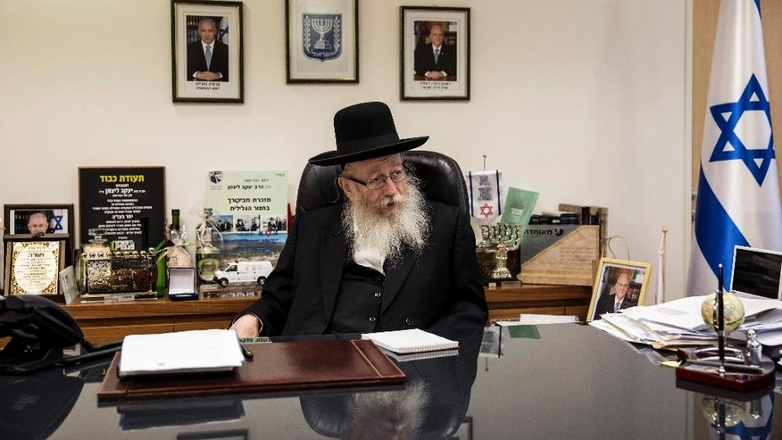 In this photo taken Wednesday, Sept. 7, 2016, Israeli Health Minister Yaakov Litzman speaks during an interview with the Associated Press in is office in Jerusalem. As the senior representative of ultra-Orthodox Jews in Israeli government, Health Minister Yaakov Litzman is unapologetic about the insular lifestyle he advocates and which has long irked mainstream Israel and endangered its long-term economic prospects. He insists that shirking military service, rejecting secular education and raising large families on state subsidies all serve the most noblest of purposes: a life devoted to the study of scripture that has preserved Jewish traditions over centuries and will ultimately bring about the coming of the Messiah. (AP Photo/Tsafrir Abayov)