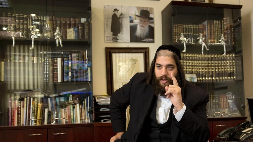 """In this photo taken Tuesday, Aug. 30, 2016 Elad's Mayor Yisrael Porush speaks during an interview with the Associated Press in his office in the city of Elad, central Israel. Mayor Porush, a 35-year-old father of six and scion of a prominent Haredi family, said his main objective was to develop the city and provide opportunities for those who wanted them. """"I'm opening the door for them and it doesn't come at the expense of study. Those who study, study. Those who work, work. I just need to give them the tools,"""" he said. """"I can't say that it is a 'change,' the world is moving forward and everyone wants to feel equal."""" (AP Photo/Sebastian Scheiner)"""
