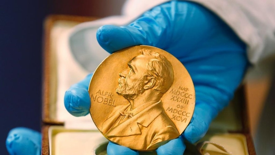 FILE- In this file photo dated Friday, April 17, 2015, a national library employee shows the gold Nobel Prize medal awarded to the late novelist Gabriel Garcia Marquez, in Bogota, Colombia.  There is no bigger international honor than the Nobel Prize, created by 19th-century Swedish industrialist Alfred Nobel, and the 2016 laureates will be named over the coming days to join the pantheon of greats who were honored in years gone by. (AP Photo/Fernando Vergara, FILE)