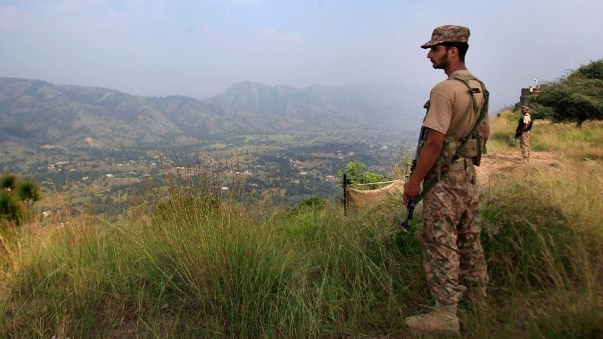 In this Saturday, Oct. 1, 2016 photo, Pakistan army soldiers monitor the area from the hilltop Bagsar post on the line of control, that divides Kashmir between Pakistan and India, near Bhimber, some 166 kilometers (103 miles) from Islamabad, Pakistan. Officials in Islamabad say Pakistan and India are trying to de-escalate border tensions after their troops exchanged several rounds of gunfire over the last week in the disputed Kashmir region. (AP Photo/Anjum Naveed)