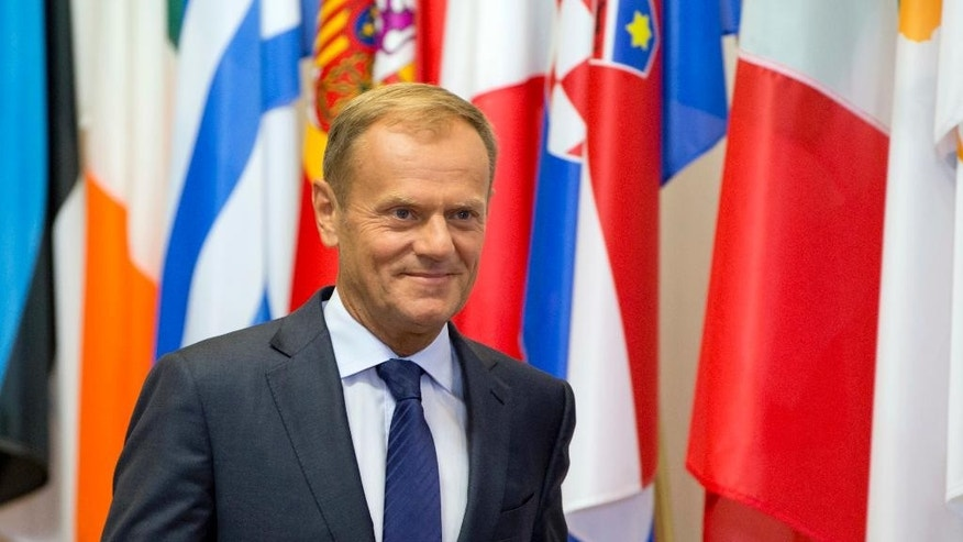 FILE - In this Sept. 2, 2016 file photo, European Council President Donald Tusk walks by flags of EU countries prior to a meeting at the EU Council building in Brussels. Poland's conservative ruling party leader said in comments published Tuesday, Oct. 4, 2016, that the government would not back Tusk for a second term as European Council head. (AP Photo/Virginia Mayo, File)