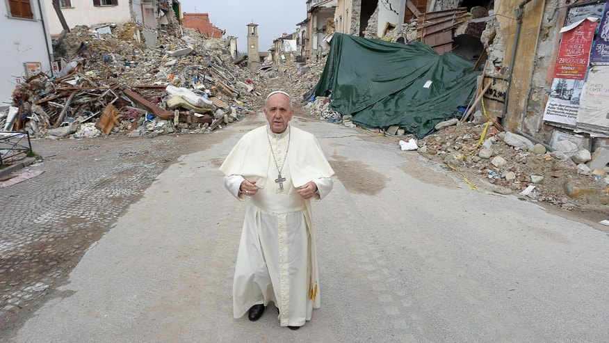 Pope Francis stands in front of rubble in the quake-struck town of Amatrice, Italy, Tuesday, Oct. 4, 2016.