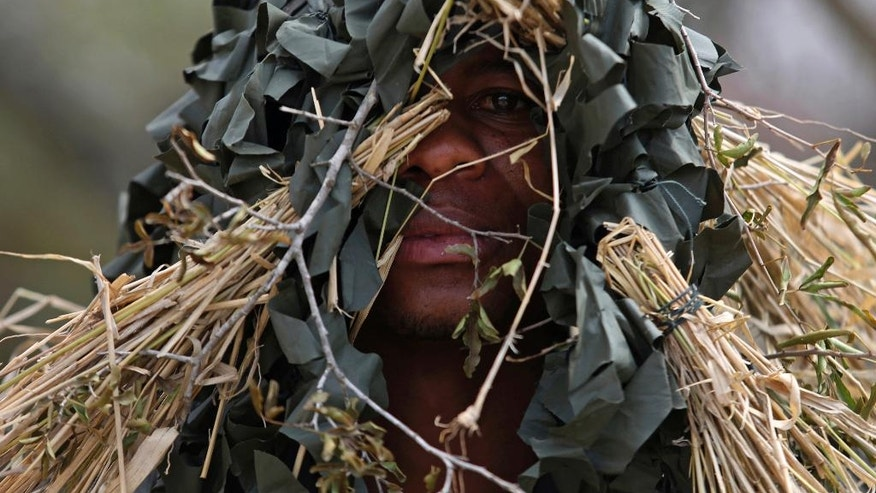 In this photo taken Saturday, Oct. 1, 2016, a recruit displays a camouflage technique at the Southern African Wildlife College on the edge of Kruger National Park in South Africa, where young men and women are trained to become field rangers and guides. As teams of poachers stalk rhinos and elephants in the park, wildlife officials are turning to nearby communities to help stop the slaughter by using local knowledge to deter poachers, not join them. (AP Photo/Denis Farrell)