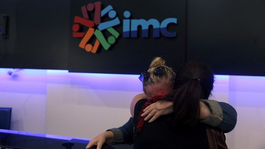 IMC TV employees react Tuesday after their broadcaster's transmission was cut.
