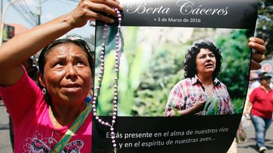 FILE - In this March 16, 2016, file photo, a woman holds up a poster with a photo of slain environmental leader Berta Caceres, during a protest march in Tegucigalpa, Honduras. Authorities said that unidentified gunmen killed Nelson Garcia, a colleague of Caceres, who was slain almost two weeks ago in similar circumstances. Honduran authorities announced Thursday, Sept. 8, that they have arrested a sixth suspect in the March killing of environmental activist Berta Caceres. (AP Photo/Fernando Antonio, File)