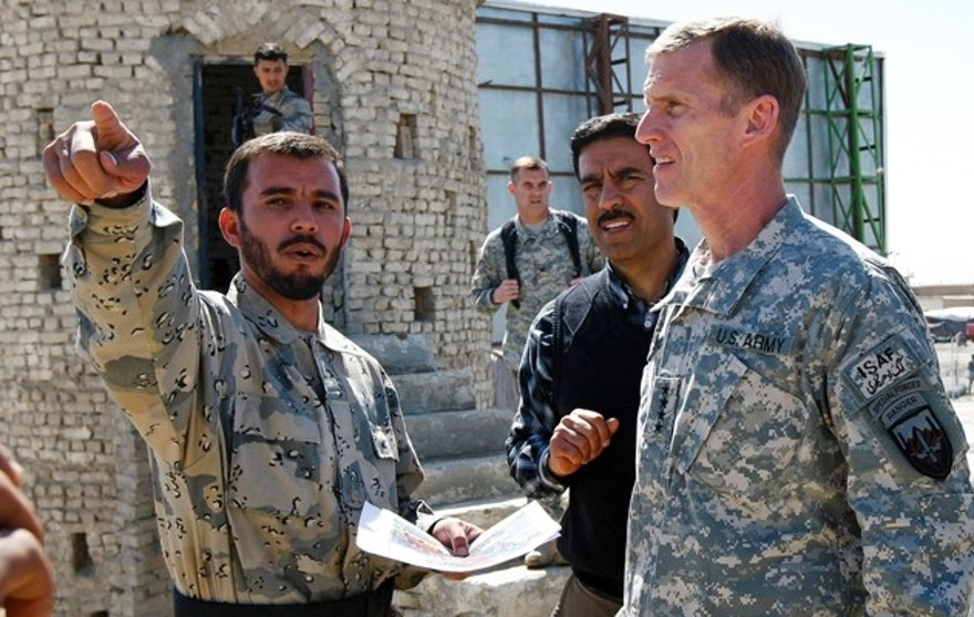 "General Stanley McChrystal (R), commander of U.S. and NATO forces in Afghanistan, receives a briefing from Afghan border police commander Colonel Abdul Razziq during a visit to the Afghan border with Pakistan, near Spin Boldak in Kandahar Province, southern Afghanistan, in this March 4, 2010 file photo. One of the most important trade routes in Asia was closed last week while a boyish-looking man everyone calls ""the general"" showed around the commander of U.S. and NATO forces in Afghanistan. Picture taken March 4, 2010.   To match feature AFGHANISTAN-BORDER/     REUTERS/Peter Graff  (AFGHANISTAN - Tags: POLITICS MILITARY CONFLICT) - RTR2BRKT"
