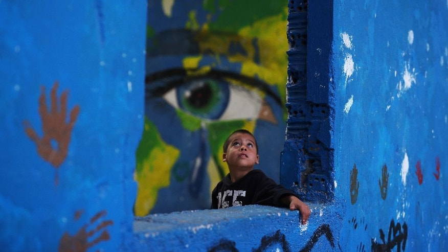 In this Tuesday, Sept. 13, 2016 photo, a Syrian child plays in front of graffiti at the Ritsona camp for refugees and other migrants north of Athens. About 600 people _ including 160 children _ live in the camp. (AP Photo/Petros Giannakouris)