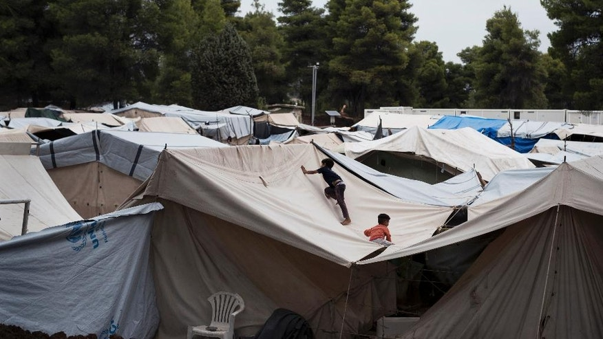 In this Thursday, Sept. 8, 2016 photo, Syrian children play on the top of a tent at the Ritsona camp for refugees and other migrants north of Athens. Like dozens of refugee camps hastily created around Greece, Ritsona started with tents set up in an abandoned military facility. (AP Photo/Petros Giannakouris)