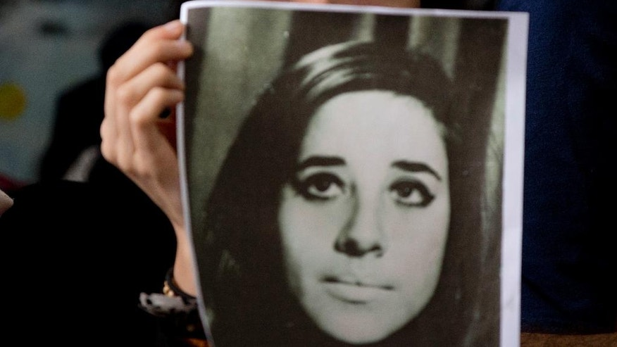 A woman holds an image of Ana Maria Lanzillotto, disappeared during the country's former dictatorship, during a press conference called by the human rights group Grandmothers of the Plaza de Mayo in Buenos Aires, Argentina, Wednesday, Oct. 5, 2016, to announce DNA tests have determined the identity of another stolen baby. The man, whose identity has not yet been revealed, is the son of Ana Maria Lanzillotto and Domingo Menna, both kidnapped by dictatorship agents in 1976. The couple remains disappeared. (AP Photo/Natacha Pisarenko)