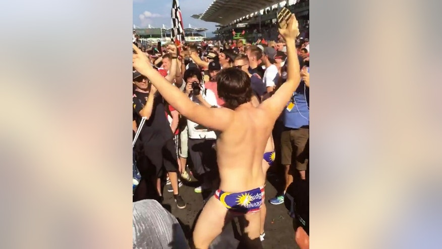In this Sunday, Oct. 2, 2016 image made from video supplied by Umar Akif Jamaludin, an Australian man dances in Budgy Smuggler-brand swimsuits decorated with the Malaysian flag at the conclusion of the Malaysian Formula One Grand Prix in Sepang, Malaysia. Nine Australians, including a government adviser, have been arrested in Malaysia for stripping down to their briefs and drinking beer from shoes after Australian driver Daniel Ricciardo won the Malaysian Formula One Grand Prix, officials said Tuesday. (AP Photo)
