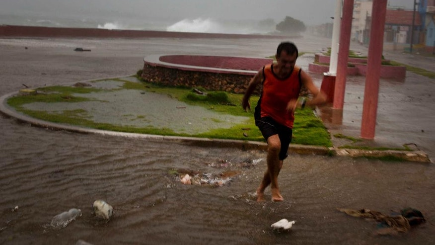 A man runs from a wave at the waterfront  in Baracoa, Cuba, Tuesday, Oct. 4, 2016. The dangerous Category 4 storm blew ashore around dawn in Haiti. It unloaded heavy rain as it swirled on toward a lightly populated part of Cuba and the Bahamas. (AP Photo/Ramon Espinosa)