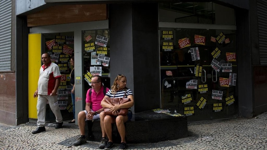 People sit outside a striking bank in Rio de Janeiro, Brazil, Wednesday, Oct. 5, 2016. The strike that began one month ago to demand a wage increase of nearly 15 percent, on Wednesday completed one month, making it the longest bank workers strike in 12 years. (AP Photo/Silvia Izquierdo)