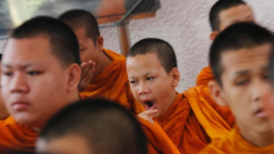 A novice Buddhist monk yawns before the start of ceremonies at Thammasat University in Bangkok, Thailand, Thursday, Oct. 6, 2016. Buddhist monks, mourners, activists and others gathered Thursday to mark the 40th anniversary of one of the darkest days in Thailand's history, when police killed scores of university students at a peaceful protest, and ghoulish vigilantes defiled the dead. (AP Photo/Sakchai Lalit)