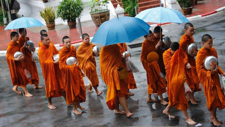 Thai Buddhist monks walk near Thammasat University in Bangkok, Thailand, Thursday, Oct. 6, 2016, as Buddhist monks, mourners, activists and others gathered Thursday to mark the 40th anniversary of one of the darkest days in Thailand's history, when police killed scores of university students at a peaceful protest, and ghoulish vigilantes defiled the dead. (AP Photo/Sakchai Lalit)