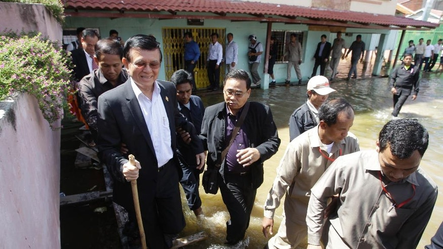 Cambodia's main opposition Cambodia National Rescue Party Deputy President Kem Sokha, left, walks through flooded as he heads for registering his name during a voter registration process of the National Election Committee (NEC) in Phnom Penh, Cambodia, Wednesday, Oct. 5, 2016. The NEC is holding its three-month-long voter registration for the next general election scheduled for July 2018. (AP Photo/Heng Sinith)