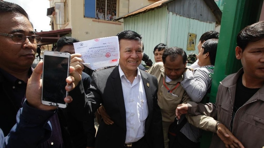 Cambodia's main opposition Cambodia National Rescue Party Deputy President Kem Sokha, center, holds a registration receipt after registering his name during a voter registration process of the National Election Committee (NEC) in Phnom Penh, Cambodia, Wednesday, Oct. 5, 2016. The NEC is hoding its three-month-long voter registration for the next general election scheduled for July 2018. (AP Photo/Heng Sinith)