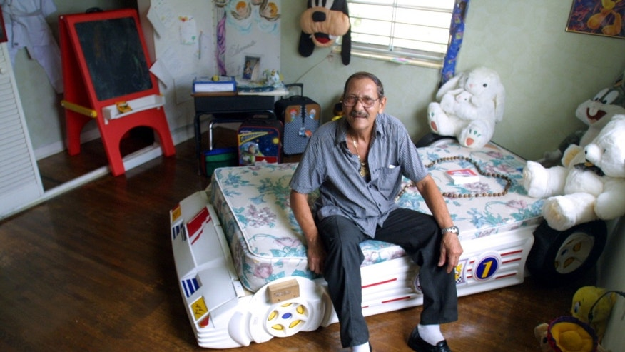 396153 05: Delfin Gonzalez, great uncle of Elian Gonzalez, sits on the bed October 19, 2001 that Elian Gonzalez slept on while in the Miami, Florida house before he was returned to Cuba. On Sunday, the former residence of the Gonzalez family will make its debut as a museum to Elian, who became a symbol to Miami's Cuban community. (Photo by Joe Raedle/Getty Images)