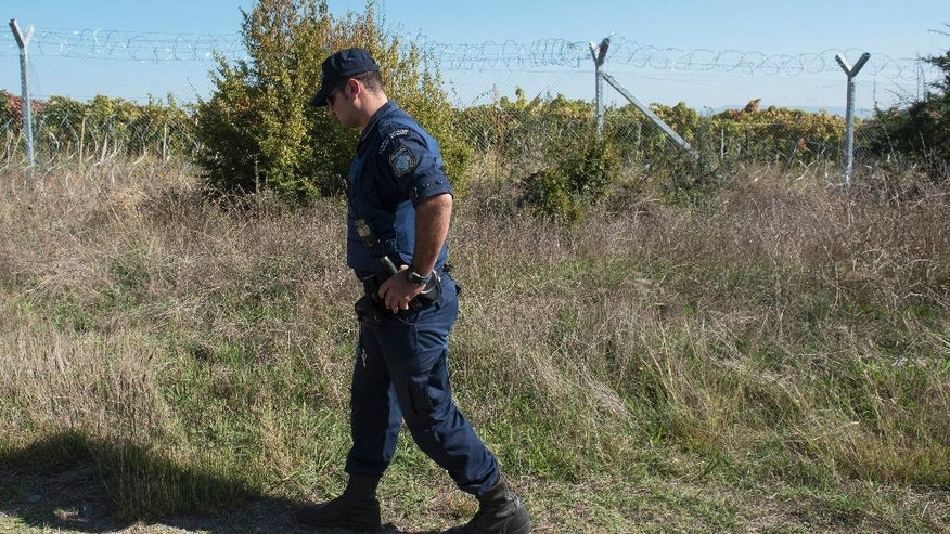 In this Monday, Oct. 3, 2016 photo, a Greek police officer patrols next to the border fence between Greece and Macedonia, near the northern Greek border station of Idomeni. Despite Macedonia's construction of a fence, dozens of people try to sneak across the border every day, hoping to make their way to Europe's prosperous heartland. Police have been detaining about 50 people daily, and arresting members of smuggling gangs that promise to get migrants to their destinations. About 60,000 refugees and other migrants are trapped in financially-struggling Greece. (AP Photo/Giannis Papanikos)